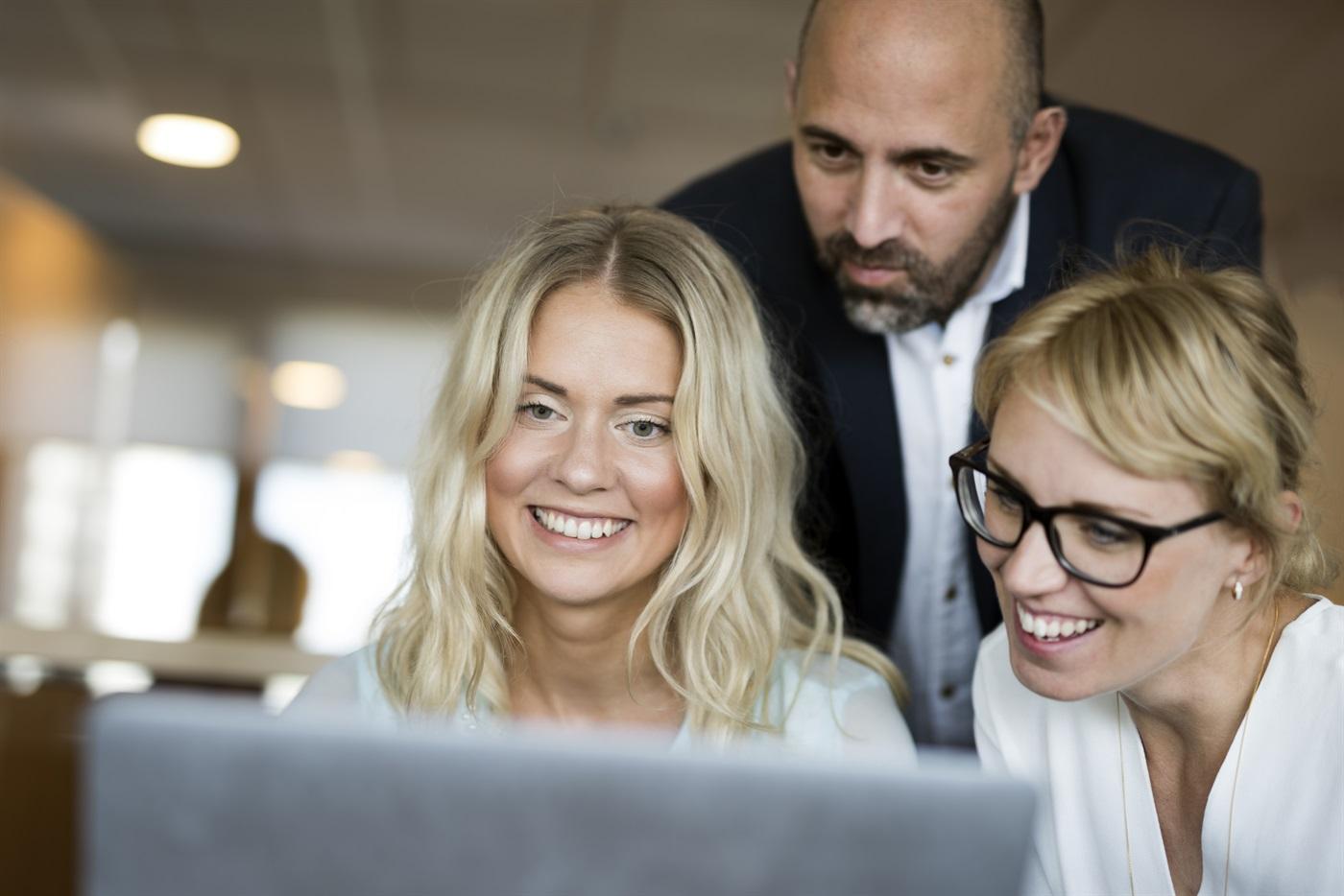 Två kvinnor och en man framför laptop